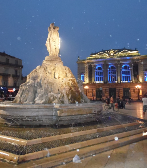 """Place de la Comédie. Na pierwszym planie słynna fontanna- """"Les trois grâces , zwyczajowy meeting point, na drugim planie Opera."""